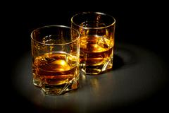 two glasses of whiskey on black table - stock photo