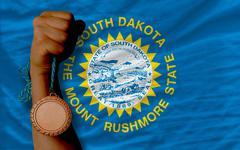 bronze medal for sport and  national flag of south dakota - stock photo