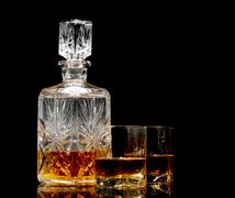 studio shot of whiskey in a carafe and glasses isolated on black - stock photo