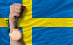 Stock Photo of bronze medal for sport and  national flag of sweden