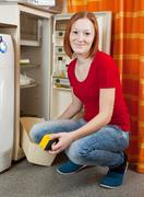 Woman  defrosting the refrigerator Stock Photos