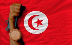 bronze medal for sport and  national flag of tunisia - stock photo
