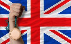 Stock Photo of bronze medal for sport and  national flag of united kingdom