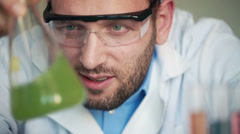 Young scientist mixing chemicals in erlenmeyer flask Stock Footage