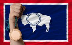 bronze medal for sport and  flag of american state of wyoming - stock photo