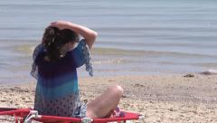 Brunette woman braids hair on the beach Stock Footage