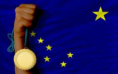 Stock Photo of gold medal for sport and  flag of american state of alaska