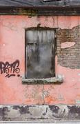 fragment of facade of an old devastated building - stock photo