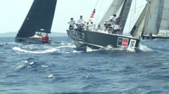 Sailing boats turning around buoy during race - stock footage
