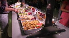Woman taking some salad at a buffet Stock Footage