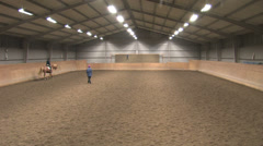 Riders taking lessons in an indoor arena Stock Footage