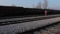 Beautiful girl walking on the railway track,tracking shot Stock Footage