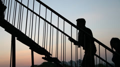 Silhouette of Lovers climbing steps Stock Footage