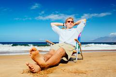 Young successful entrepreneur relaxing on the beach Stock Photos