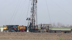 Oilfield with workers and land drilling rig Stock Footage