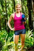 athletic woman drinking water before run - stock photo