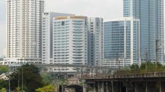Malaysia Kuala Lumpur KL Rapid KL Train passing high rise skyscrapers building Stock Footage