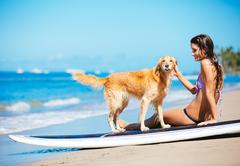 Young woman enjoying sunny day at the beach with her dog Stock Photos