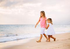 two little girls walking together on the beach at sunet - stock photo