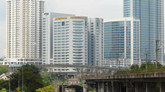 Time Lapse Malaysia Kuala Lumpur KL Rapid KL Train passing high rise skyscrapers Stock Footage