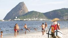 A group of boys play football in front of the Sugarloaf. Stock Footage