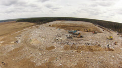 Trucks managing garbage in a landfill site, air view Stock Footage
