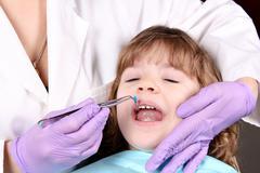 Dentist treats tooth little girl Stock Photos