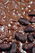 Chocolate icing with cocoa beans - stock photo