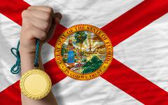 gold medal for sport and  flag of american state of florida - stock photo