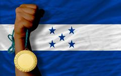 gold medal for sport and  national flag of honduras - stock photo
