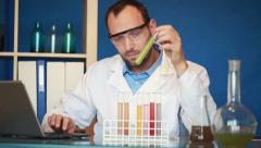 Scientist examine chemicals in test tubes, writing results on laptop HD Stock Footage