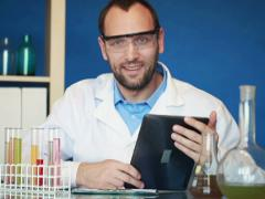 Portrait of young happy scientist with tablet computer in laboratory NTSC Stock Footage