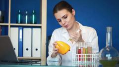 Female biochemist injecting substance into yellow pepper HD Stock Footage