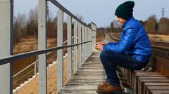 Teenage throw stones from the railway bridge Stock Footage