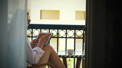 Young woman with touchpad on hotel balcony - stock footage