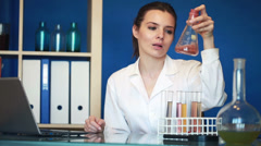 Young female chemist working with laptop and chemicals in lab HD Stock Footage