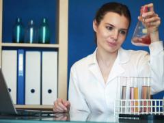 Young female chemist working with laptop and chemicals in lab NTSC Stock Footage