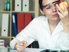 Female biochemist examine apple and writing results in lab NTSC Stock Footage