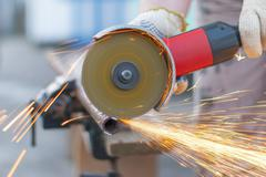 Sparks flying metal cutting abrasive disk. Stock Photos