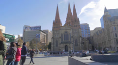 Some tourists at Federation square in front of a chapel Stock Footage
