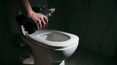 Pouring out cola into the toilet - stock footage