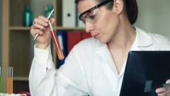 Woman tablet write compare test tubes lab K HD Stock Footage