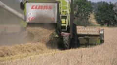 Harvesting combine threshing stalk miller machine in field Stock Footage