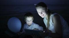 Kid with mom on the beach at night Stock Footage