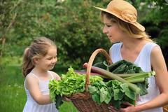 Young woman and daughter with fresh vegetable - stock photo