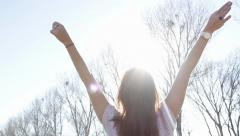 Woman in the outdoors with arms wide open under the sunlight Stock Footage