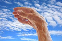 Senior woman's hand over sky Stock Photos