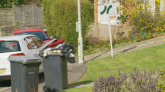 Overloaded wheelie bin next to SOLD sign Stock Footage