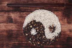 black and white rice forming a yin yang symbol. - stock photo