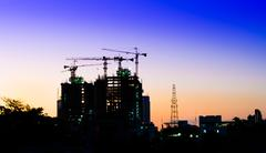Construction site with cranes at sunset Stock Photos